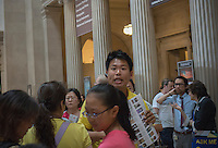 Asian tour group leader with his group in the lobby of the Metropolitan Museum of Art in New York on Sunday, July 28, 2013. (© Richard B. Levine)