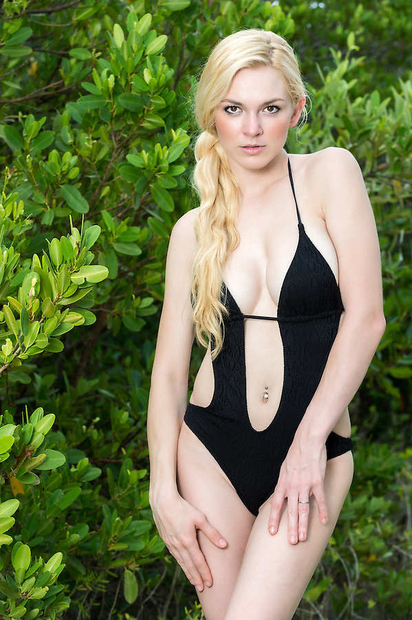 Young caucasian woman  in swimsuit looking at camera with a green leaves backgraound.