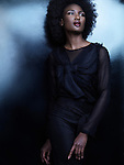 Beautiful african american woman wearing black clothes on shiny black background. High fashion photo.