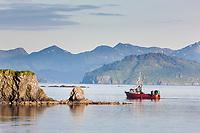 Fishing boat cruises the waters near the Kodiak harbor on the island of Kodiak, Alaska.