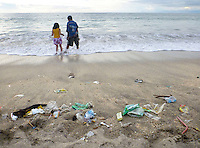 Plastic and other garbage litter the famous Kuta beach on Bali, as two children enjoy the water. Enormous amounts of litter wash up every day, especially in the rainy season.