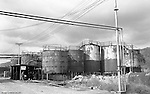 Lawrenceville PA: Location photography at the Atlantic Refining site at 5733 Butler Street. View of workman moving a barrel of oil next to storage tanks.<br />