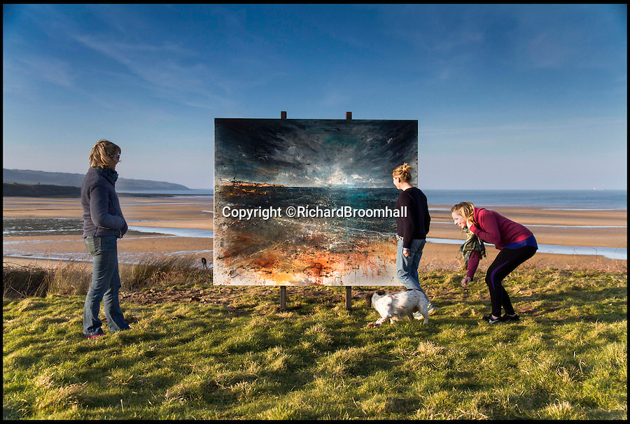 BNPS.co.uk (01202 558833)<br /> Pic: RichardBroomhall/BNPS<br /> <br /> Artist in Residence...Public art - walkers view the Lligwy Bay work.<br /> <br /> Artist Anthony Garratt is giving a whole new meaning to landscape painting - his incredible pieces aren't just of the landscape, they're in it too.<br /> <br /> The 35-year-old painter from Bristol has created four canvasses on the island of Anglesey as part of a new outdoor art installation and the paintings will remain in the exact spot they were painted until October.<br /> <br /> Mr Garratt spent several days on each of the giant 8ft-wide scenes, which are exposed to the elements and can be enjoyed by walkers as well as art fans. <br /> <br /> The landscapes had to be created on marine board - a thick marine plywood treated with sealant and epoxy, like a boat - rather than normal canvas, coated with five layers of varnish afterwards and mounted on bespoke steel frames to ensure they survive any harsh outdoor conditions.