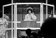 Manhattan, New York City, NY. June 29th 1972.<br /> American radical activist Angela Davis speaking at Madison Square Garden in New York. A part of several nationwide appearances by her to help pay the cost of her recent California trial on murder and conspiracy charges. She is protected during the meeting by a four sided bullet proof shield because she fears an assassination attempt.