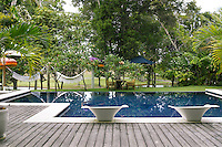 The outdoor swimming pool is surrounded by jasmine and mango trees