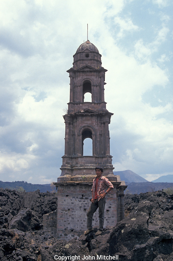 A Purepecha guide standing in front of the bell tower of the ruined Templo de San Juan Parangaricutiro near Angahuan, Michoacan, Mexico. In 1943, this church was half-buried by a lava flow from nearby Volcan Paricutin.