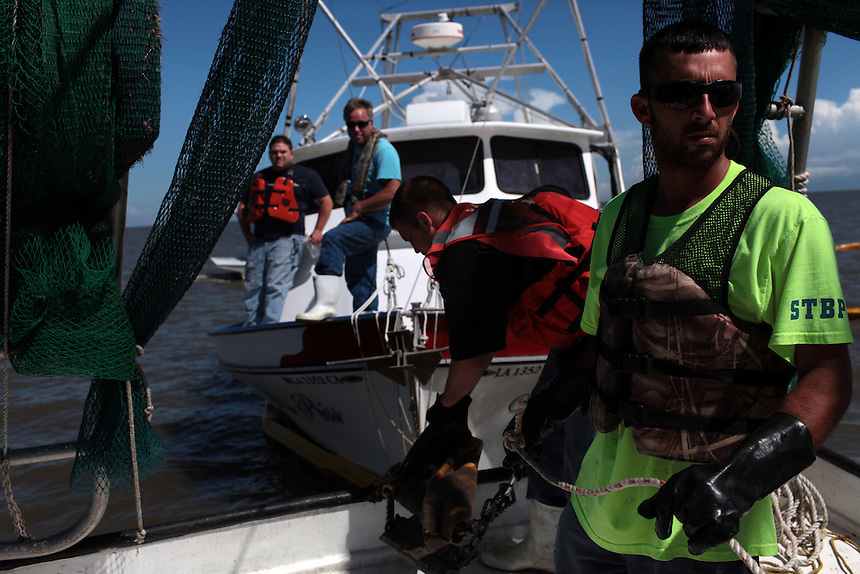 Mikey Labat and his brother Allen Labat pulling in hard boom around Pelican Island from Delacroix Island, LA August 30, 2010.