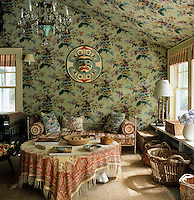 A Native American moon mask looks down on a daybed and shawl-covered table in this floral bedroom