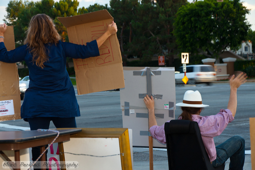 Two Occupy Orange County protesters hold signs on the corner of Harvard and Alton in Irvine, CA.