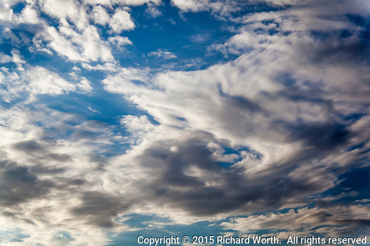 Clouds, left overs from a storm system that was once a hurricane,  open and allow sunshine in - the storm has passed.