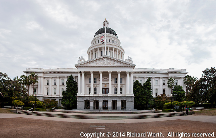 In addition to being the state's seat of government, the California State Capitol and its grounds are a California State Park - The California State Capitol Museum.  Grounds in front are brown due to the drought.  Flags are at half-staff in honor of slain Pomona Police Department Officer Shaun Diamond.  Multiple images have been combined into a wide panoramic of the capitol.