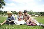 ROBERT WALKER, 4, of Coram (left), JULIAN LYNN ZOLL, 6, of Levittown (center), and MADELYN WALKER, 7, of Coram (right), wear clothes of American Civil War era while portraying family members of Union soldiers at Camp Scott re-creation, at Old Bethpage Village Restoration, to commemorate 150th Anniversary of American Civil War, on Saturday, July 21, 2012, in Old Bethpage, New York, USA.