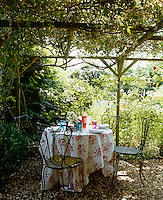 Under a pergola smothered in climbing roses a table is laid for lunch in the garden