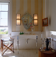 A marble washstand in this elegant bathroom with light fittings which were salvaged from a disused cinema