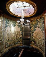 A chandelier hangs from a gilt-framed ceiling lantern above this stairwell the walls of which are covered in tapestries