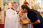 Liturgy service at St. Sava Orthodox Church, Jackson, Calif...Father Stephen Tumbas assisted by Dan Stojanovich present bread as Miloje Milinkovic kisses the golden cross in respect.