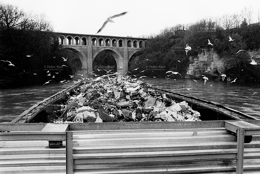 "Switzerland. Geneva. Garbage collectors. A barge, fully loaded with garbage, will sail down the current on the river Rhône to ""Les Cheneviers"" which is the incinerating plant, distant 25 km from the town. Bilds are flying over the garbage heap. © 1991 Didier Ruef"