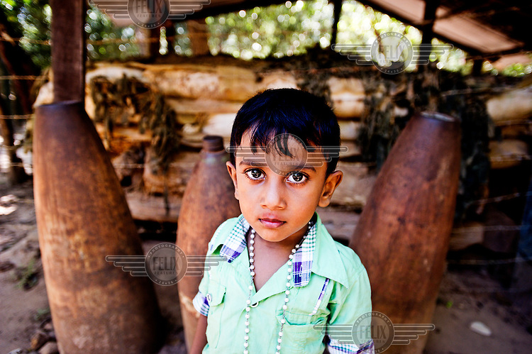 A young Tamil boy stands in front of LTTE mortar shells in Mullaitivu district.