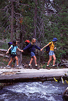Three young girls crossing a log over Prosser Creek, CA.