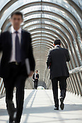Businessmen walking across covered walkway,la Defense, Paris.
