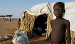 A boy in an informal camp for families displaced by fighting in the Darfur region of Sudan between government forces, Arab militias, and rebel soldiers.