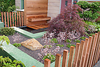 Beautifully landscaped entry of house with Japanese maple tree, Saxifraga in flowers, fence, stones, boulders, wood and upscale touches creating a sense on an outdoor room enclosed by open posts. Small garden design, pebble mulch, simplicity, saxifraga plants.