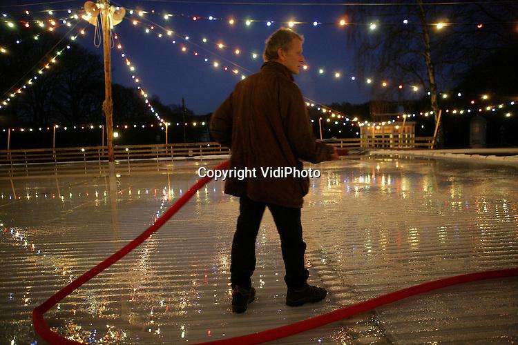 """ARNHEM - Personeel van het Nederlands Openluchtmuseum in Arnhem werkt woensdagavond aan de inrichting van de Oud-Hollandse ijsbaan. Hoewel het museum in de winterperiode gesloten is, gaan de deuren vanaf 2 december tot 14 januari open om de winters van vroeger weer tot leven te brengen. Het Openluchtmuseum spreekt van een """"waanzinnig succes"""". Vorig jaar trok het evenement in zes weken tijd 65.000 bezoekers. Foto: VidiPhoto"""