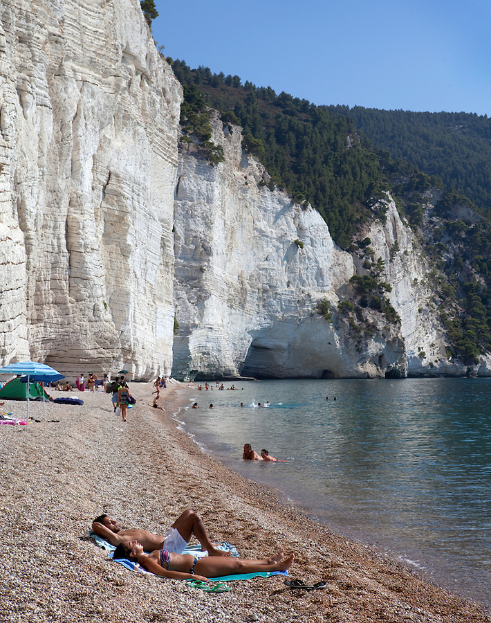 Couple sunbathing on summer vacation,  Gargano Peninsula, Puglia, Italy