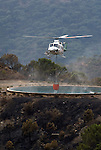 Bell helicopter with fire fighting water balloon attached refilling on a mountainside tank, Esteopna, Andalucia, Spain.