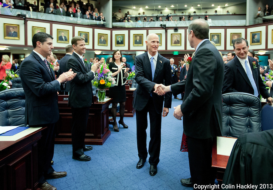 TALLAHASSEE, FLA. 3/5/13-OPENING030513CH-Gov. Rick Scott, center, greets Sen. Wilton Simpson, R-New Port Richey, right, as he enters the House Chamber to give the State of the State address during the opening day of the 2013 legislative session Tuesday at the Capitol in Tallahassee, Fla...COLIN HACKLEY PHOTO