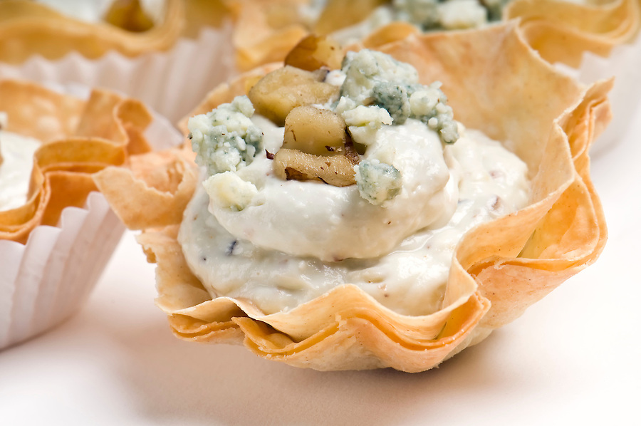 Group of Blue Cheese and walnut Volauvent. Volauvent is a tiny round canapé made of puff pastry. The term ' vol au vent ' means ' blown by the wind ' in French.