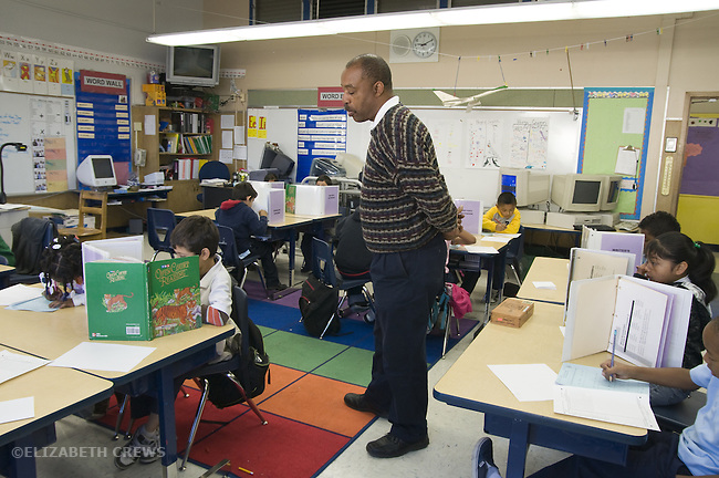 Oakland CA  2nd grade African American male teacher looking over students as they work on Oakland School District standardized test