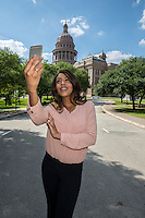 Young businesswoman taking a selfie portrait with her mobile phone against the Texas State Capitol in downtown, Austin, Texas.