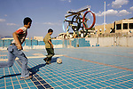 Young Iraqi boys play soccer in an abandoned swimming pool built during Saddam's regime. The facility is now used by families who cannot afford rent as a temporary home. ..Stability and security prevail in postwar Iraqi Kurdistan as Iraqi tourists, many of them from Baghdad, flock to the northern cities and their amusement parks and national parks to escape violence and sectarian strife in the central and southern regions of the country.
