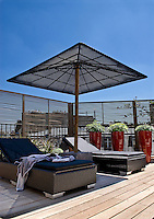 The parasol and sun loungers on this terrace are made from woven resin while a bank of slatted screens ensures privacy