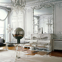 The ornamental mirror, cornice and fireplace in this period living room have been picked out in silver leaf, a glamourous backdrop for a pair of 1927 Wassily chairs by Marcel Breuer and a Perspex table with a granite top on which is displayed a mirrored ball