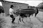 A Zapotec Native neighbor drives his donkey carrying a hose in Coatecas Altas village, Oaxaca, November 22, 1998. Most of the villagers of Coatecas leave their home to harvest in northern state of Sinaloa.  © Photo by Heriberto Rodriguez