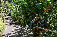 Tourists rest on a bench at Hawai'i Tropical Botanical Garden, Onomea, Big Island of Hawaiʻi.