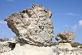 Sarakiniko White Tuff formations, Milos, Greece. These were emplaced in a submarine environment and subsequently uplifted by volcano-tectonic processes. The mushroom-shaped rock formations formed by protection of tuff from weathering by harder rock deposited above.