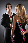 Young man holding a red rose and a woman holding a knife behind her back. Adultery, betrayal concept.