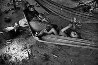 A Nukak woman with her children lies in a hammock in a refugee encampment close to San Jose del Guaviare, Colombia, 4 September 2009. The Nukak Maku people, nomadic hunter-gatherers from Amazonia, were violently driven out of the jungle by the Colombian guerilla and paramilitary squads. Now, roughly cut off their original tribal lifestyle, they stuck between worlds. They learn from the (mainly Christian) aid workers to use clothes, to listen to the radio, to beg for money. Although their digestion suffer, they love to eat sweets, cookies and other western food. They have hunted out all the animals around and now there is nothing left for them. Nukak can not return to the jungle, their world has already passed through an irreversible change.