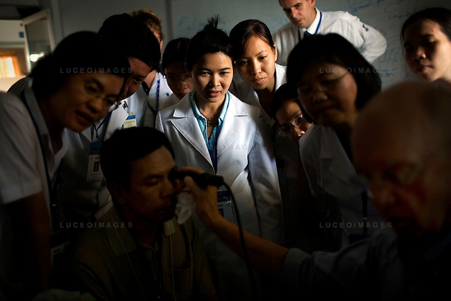Vietnamese doctors watch as Dr. Steve Charles, right, performs an ultrasound on a patient's eye to see the extent of retinal damage he is suffering from during a screening day at the Ho Chi Minh City Eye Hospital on Monday, April 14, 2008. Doctors Phung Nguyen, middle left, and Ha Nguyen, middle, right. ..ORBIS Flying Eye Hospital brought doctors, nurses and specialists from all over the world to Ho Chi Minh City, Vietnam from April 7-18, 2008.  The ORBIS program contributed to the efforts of Ho Chi Minh City Eye Hospital in fighting avoidable blindness by educating local ophthalmologists to diagnose and manage pediatric blindness, retinal disease, oculoplastics, and blindness due to glaucoma.