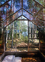 The glass house is decorated with a mosaic of tree trunk sections and is an idyllic space in which to sleep out under the stars