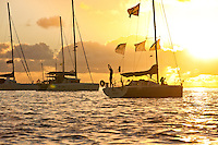 Man stretching on yacht at sunrise in lagoon off Tahaa Island, with woman on bow