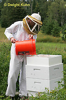 1B15-533z  Person tending honeybee hive