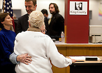 Jane Abbott Lighty, white sweater, and Pete-e Petersen, facing camera, who have been together for 35 years, sneak a hug before the issuing of marriage licenses begins. Shortly after midnight, December 6th, 2012, King County Executive Dow Constantinebegan to issue marriage licenses to same-sex couples in Seattle. Jane: ?To have our 35 year loving relationship publicly honored and celebrated and have this be a legal marriage means everything to both of us.? In the background are Anne Levinson and King County Councilmember Joe McDermott.