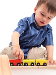 Two year old boy plaing with a wooden toy train on a railroad