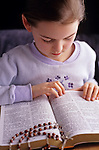 Young girl in prayer reading the bible with a rosary on the bible Bothell Washington State USA  MR...
