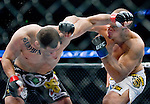Junior Dos Santos, white trunks, connects hard with Cain Velasquez in the World Heavyweight Championship match during Saturday's UFC on Fox.