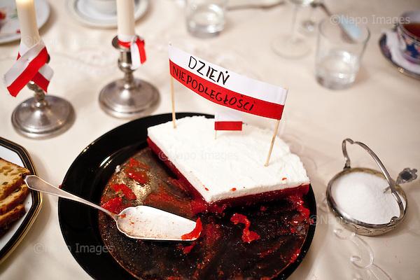 """Warszawa, Poland, November 11, 2011:.A patriotic cake on table during the Polish Independence Day dinner at one of Warsaw homes. Miniature Polish flag bears writing """"Dzien Niepodleglosci"""" (""""Independence Day"""").(Photo by Piotr Malecki / Napo Images)..Warszawa, 11/11/2011:.Patriotyczny tort i zastawa stolowa podczas urodzystego obiadu z okazji Dnia Niepodleglosci..Fot: Piotr Malecki / Napo Images."""